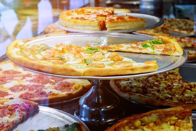 Pizza, die auf einem pizzeriazähler mit italienischem pizzazähler des sonnenlichts stillsteht