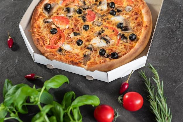 Pizza, essen, gemüse. gemüse-, pilz- und tomatenpizza auf einem dunklen hintergrund. es kann als hintergrund verwendet werden
