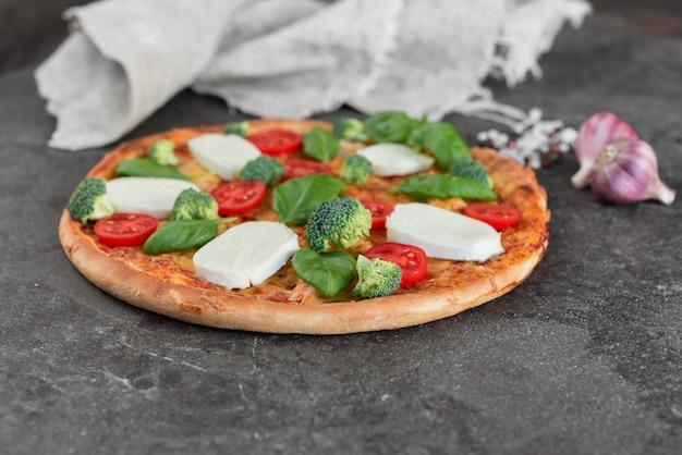 Pizza, essen, gemüse. gemüse-, pilz- und tomatenpizza auf einem dunklen hintergrund