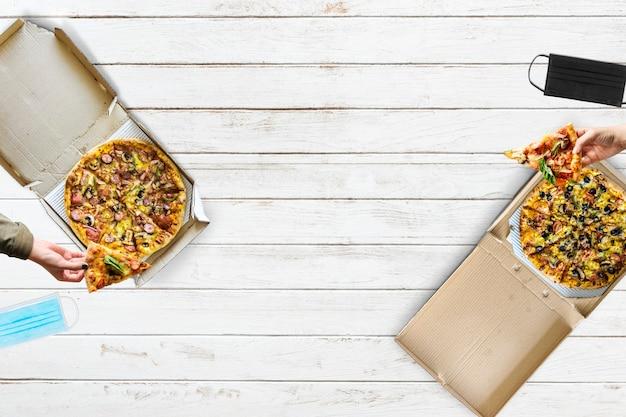 Pizza essen mit sozialer distanzierung auf die neue normale art und weise