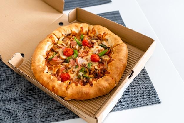 Pizza für eine person. mini-pizza in einer box. lebensmittellieferservice.