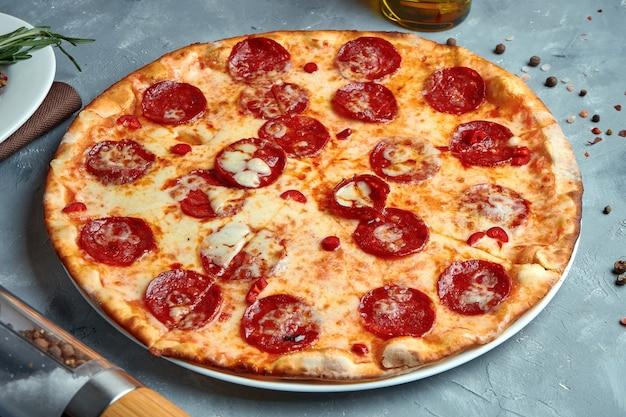 Pizza gebacken in einem holzofen mit geschmolzenem käse und chorizo-salami auf einem grau