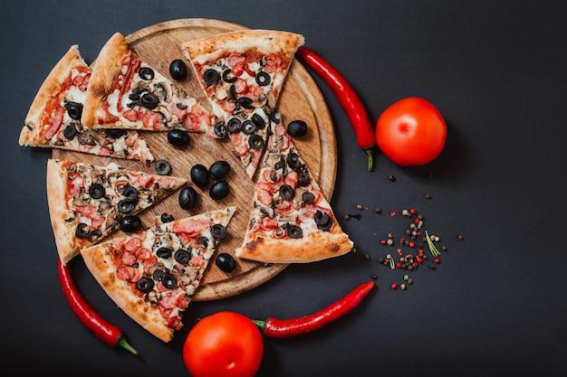 Pizza gefüllt mit tomaten, rotem pfeffer, salami und oliven