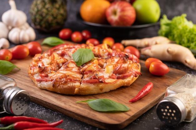 Pizza in einem holztablett mit tomaten chili und basilikum.