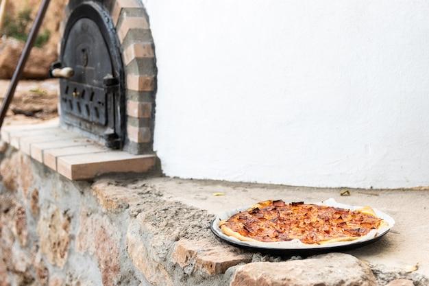 Pizza in einem weiß lackierten handwerklichen holzofen, der von außen gebaut wurde, hintergrund
