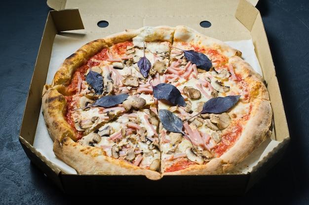 Pizza in einer pappschachtel, dunkler hintergrund. pizza-menü.