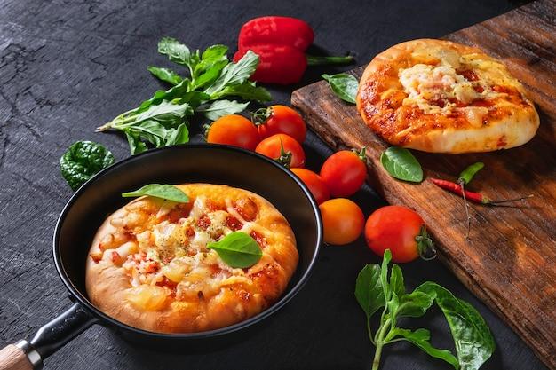 Pizza in einer pfanne mit pizza auf einem hölzernen tablett