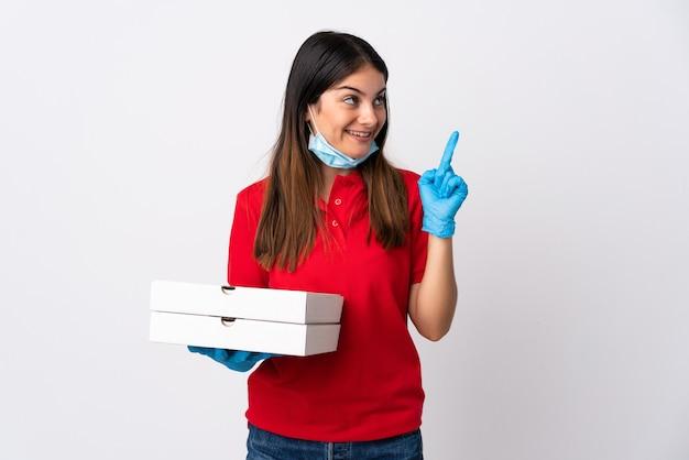 Pizza-lieferfrau, die eine auf weiß isolierte pizza hält, die beabsichtigt, die lösung zu realisieren, während sie einen finger anhebt
