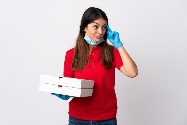 Pizza-lieferfrau, die eine pizza hält, die auf weiß lokalisiert wird, das zweifel und mit verwirrendem gesichtsausdruck hat