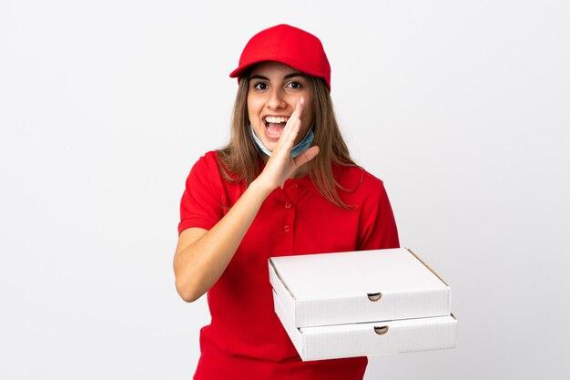 Pizza-lieferfrau, die eine pizza hält und vor dem coronavirus mit einer maske auf isolierter weißer wand schützt, die etwas flüstert