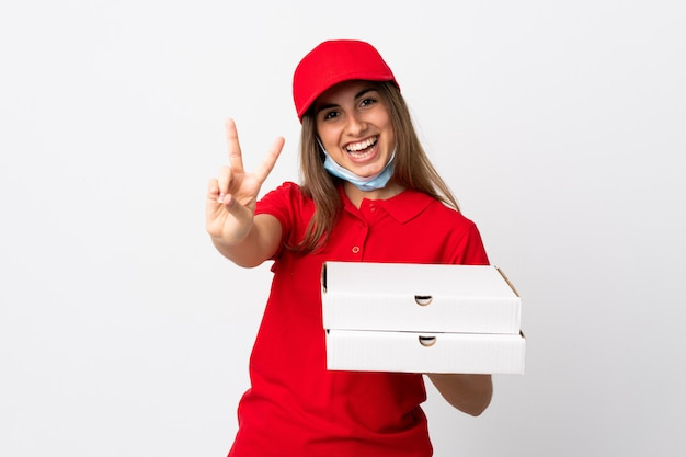 Pizza-lieferfrau, die eine pizza hält und vor dem coronavirus mit einer maske über der isolierten weißen wand schützt, die lächelt und siegeszeichen zeigt