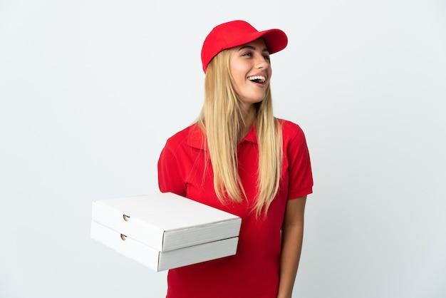Pizza-lieferfrau, die eine pizza lokalisiert auf weißem lachendem wand hält