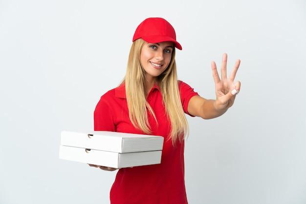 Pizza-lieferfrau, die eine pizza lokalisiert auf weißer wand glücklich hält und drei mit den fingern zählt