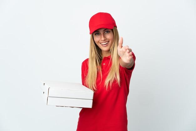 Pizza-lieferfrau, die eine pizza lokalisiert auf weißer wand hält, die hände für das schließen eines guten geschäfts schüttelt