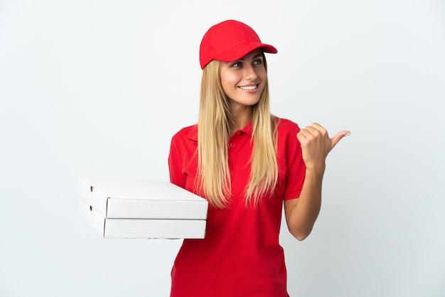 Pizza-lieferfrau, die eine pizza lokalisiert auf weißer wand hält, die zur seite zeigt, um ein produkt zu präsentieren