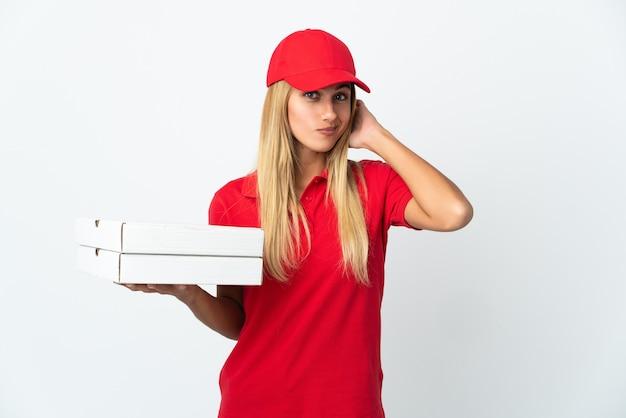 Pizza-lieferfrau, die eine pizza lokalisiert auf weißer wand hält, die zweifel hat