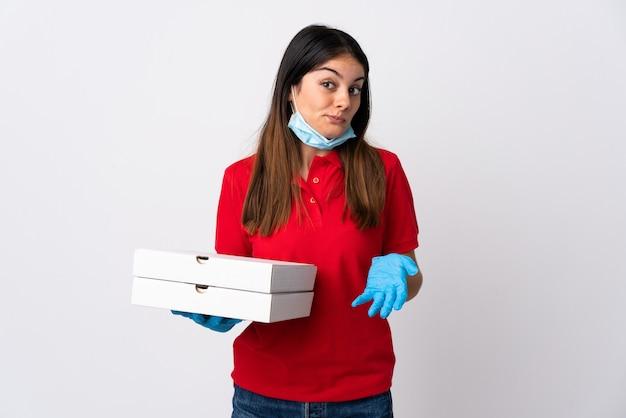 Pizza-lieferfrau, die eine pizza lokalisiert hält, die auf weiß isoliert wird, macht zweifel, während sie die schultern anhebt