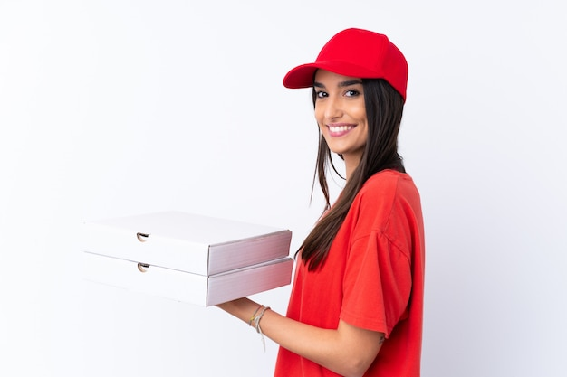 Pizza-lieferfrau, die eine pizza über isolierte weiße wand hält, die viel lächelt