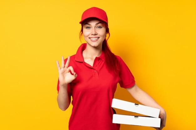 Pizza-lieferfrau, die eine pizza über isolierter wand hält, die ok zeichen mit zwei händen zeigt