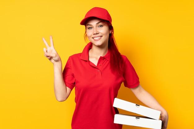 Pizza-lieferfrau, die eine pizza über isolierter wand hält, die siegeszeichen mit beiden händen zeigt