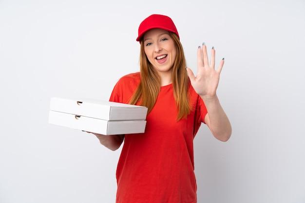 Pizza-lieferfrau, die eine pizza über rosa wand hält, die mit hand mit glücklichem ausdruck salutiert