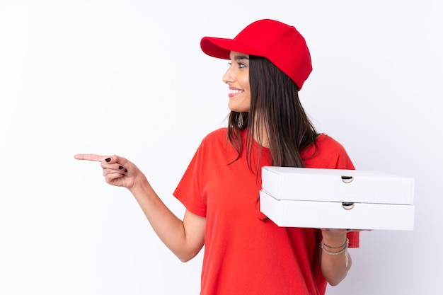 Pizza-lieferfrau, die eine pizza über weißer wand hält, die zur seite zeigt, um ein produkt zu präsentieren