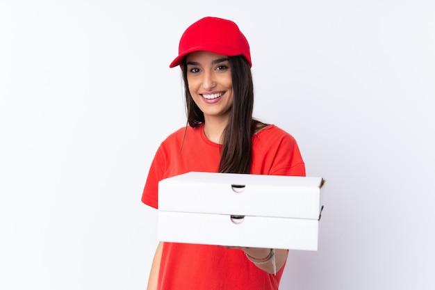 Pizza-lieferfrau, die eine pizza über weißer wand mit glücklichem ausdruck hält