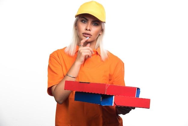 Pizza-lieferfrau, die pizza auf weißem hintergrund beim denken hält. hochwertiges foto