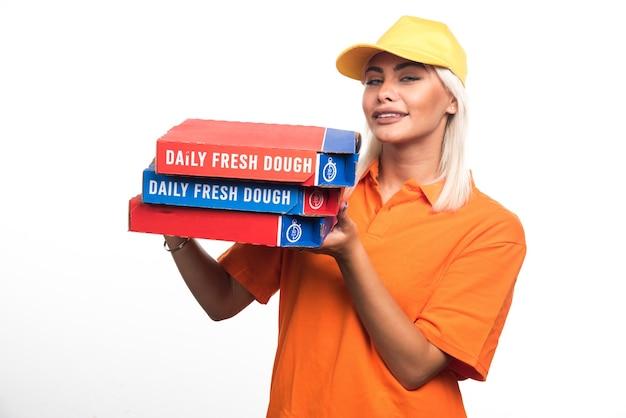 Pizza-lieferfrau, die pizza auf weißem hintergrund beim schauen hält. hochwertiges foto
