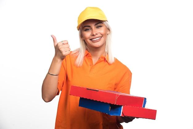 Pizza-lieferfrau, die pizza auf weißem hintergrund hält, der daumen hoch geste aufgibt. hochwertiges foto