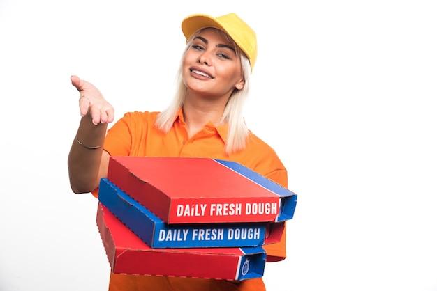 Pizza-lieferfrau, die pizza auf weißem hintergrund hält, der hand zeigt. hochwertiges foto
