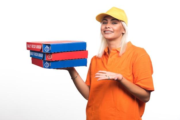 Pizza-lieferfrau, die pizza auf weißem hintergrund hält, die hände zur seite ausdehnt. hochwertiges foto
