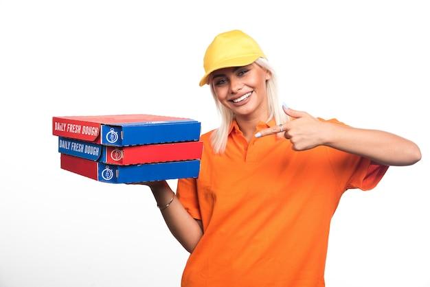 Pizza-lieferfrau, die pizza auf weißem hintergrund hält und finger zur seite zeigt. hochwertiges foto