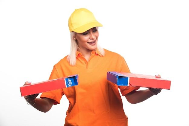 Pizza-lieferfrau, die pizza auf weißem hintergrund hält, während sie sie betrachtet. hochwertiges foto