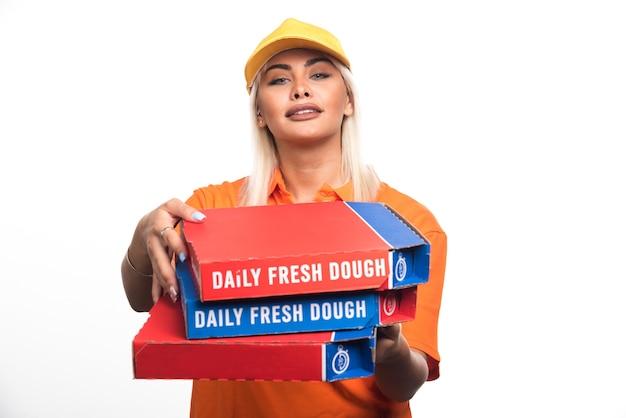 Pizza-lieferfrau, die pizza auf weißem hintergrund mit glücklichem ausdruck hält. hochwertiges foto