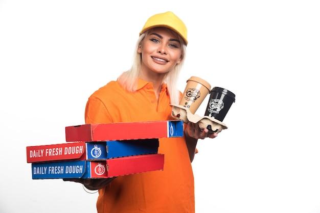 Pizza-lieferfrau, die pizza und kaffee auf weißem hintergrund hält. hochwertiges foto