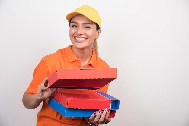 Pizza-lieferfrau, die pizzaschachteln auf weißem hintergrund hält.