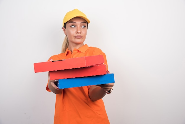 Pizza-lieferfrau, die pizzaschachteln mit friedlichem gesicht auf weißem hintergrund hält.