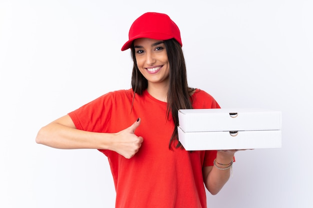 Pizza-lieferfrau hält eine pizza über weißer wand mit daumen hoch, weil etwas gutes passiert ist
