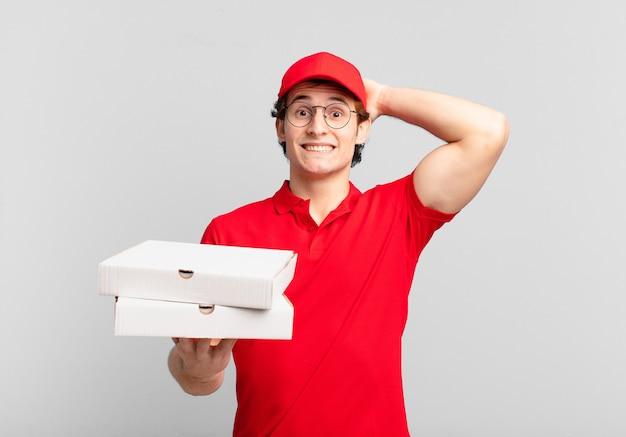 Pizza liefern jungen, die sich gestresst, besorgt, ängstlich oder ängstlich fühlen, mit den händen auf dem kopf und bei fehlern in panik geraten