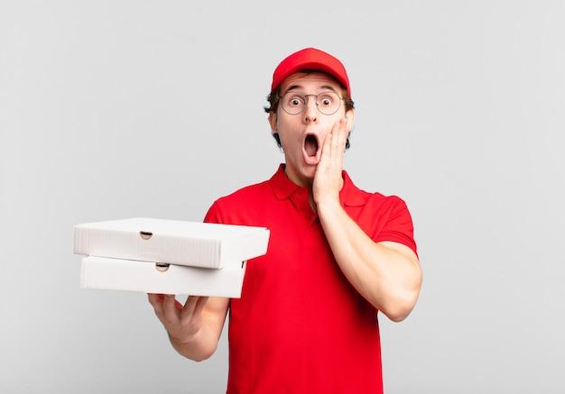 Pizza liefern jungen, die sich schockiert und verängstigt fühlen und mit offenem mund und händen auf den wangen verängstigt aussehen