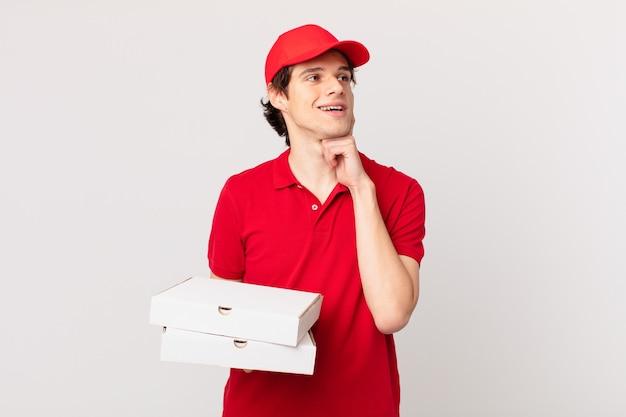 Pizza liefern mann glücklich lächelnd und tagträumen oder zweifeln