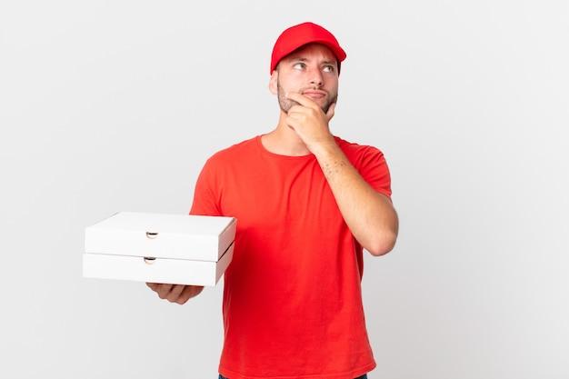 Pizza liefert mann, der denkt, sich zweifelnd und verwirrt fühlt