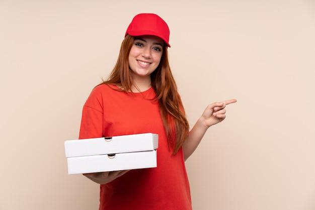 Pizza lieferung teenager-mädchen hält eine pizza über isolierte wand zeigt finger zur seite