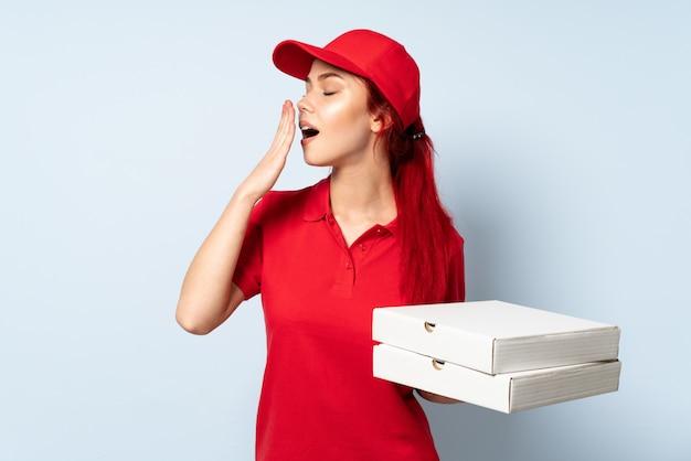 Pizza-lieferungsmädchen, das eine pizza über isoliertem hintergrund hält, der gähnt und weit geöffneten mund mit hand bedeckt