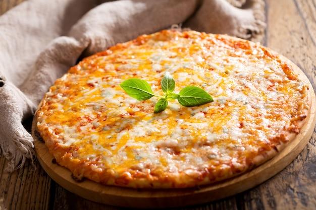 Pizza margarita mit grünem basilikum auf holztisch