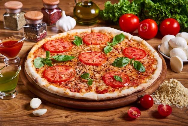 Pizza margarita mit tomatensauce, frischem mozzarella, parmesan und basilikum