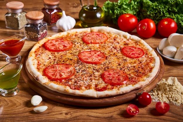 Pizza margarita mit tomatensauce, frischem mozzarella, parmesankäse auf dem hölzernen rostigen. heiße große pizza, leckere pizza-komposition