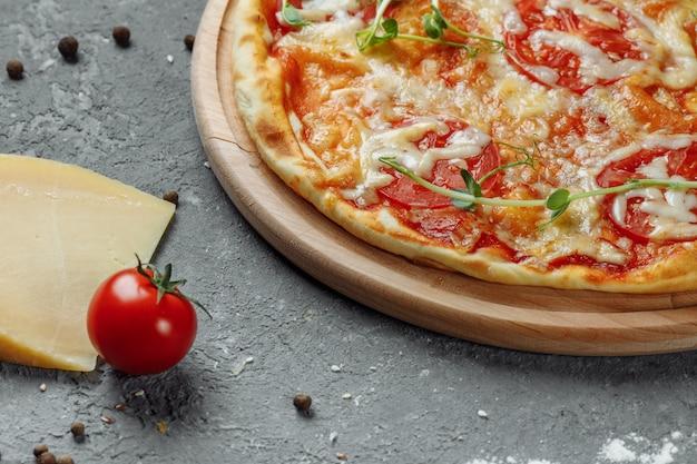Pizza margherita auf schwarzem steinhintergrund, draufsicht. pizza margarita mit tomaten, basilikum und mozzarella-käse hautnah