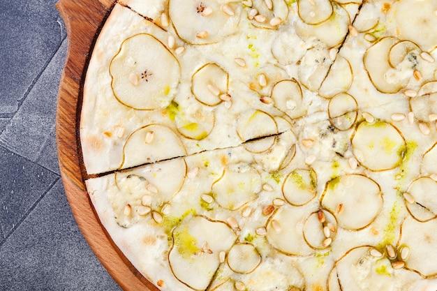 Pizza mit birnen und blauschimmelkäse auf einem holzbrett. nahansicht
